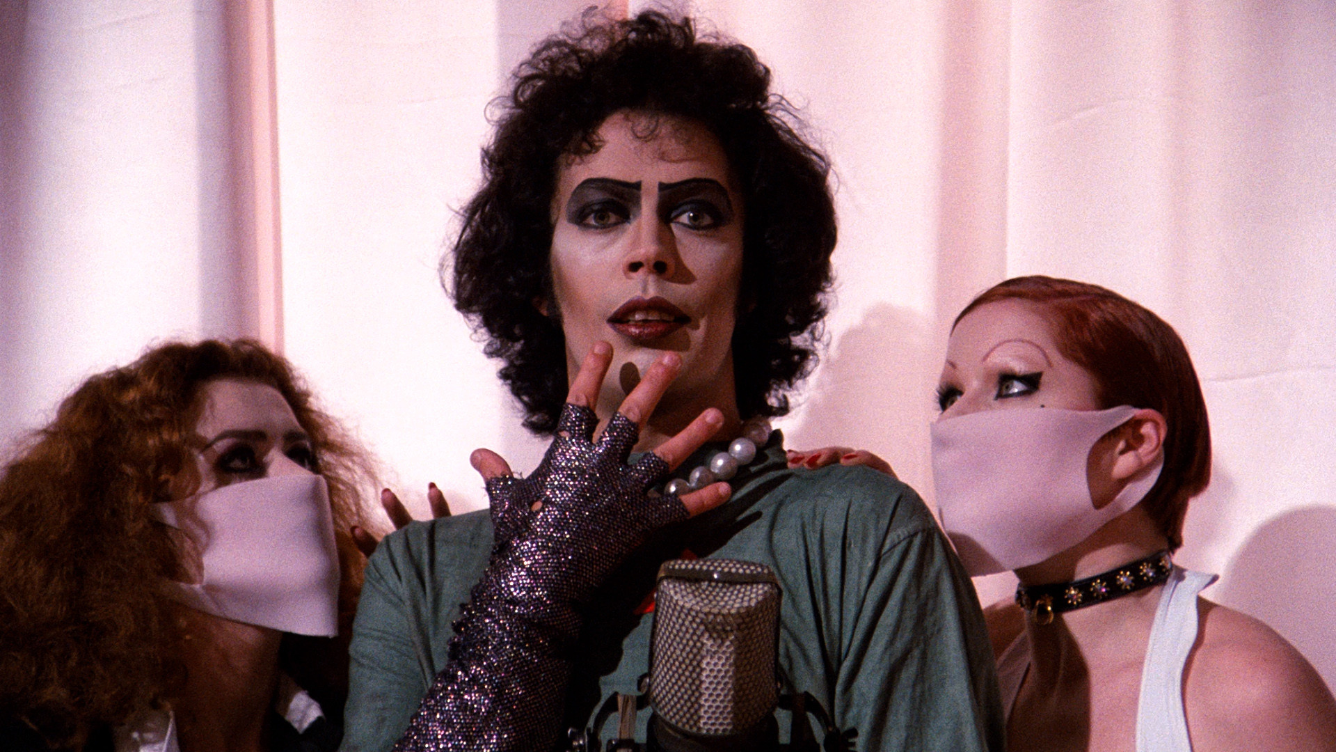 Frank N. Furter (Tim Curry) surrounded by Magenta (Patricia Quinn) and Columbia (Nell Campbell) in surgical masks.
