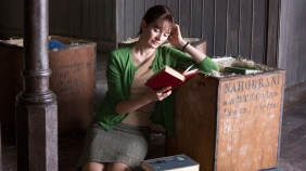 Emily Mortimer leaning against a crate of books, reading.