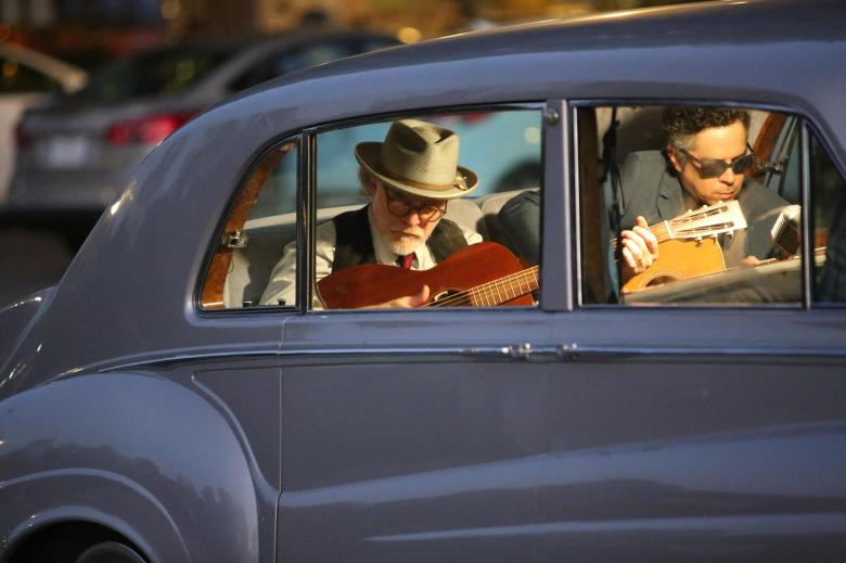 Two guitar players, guitars in hand, sitting in Elvis' car.