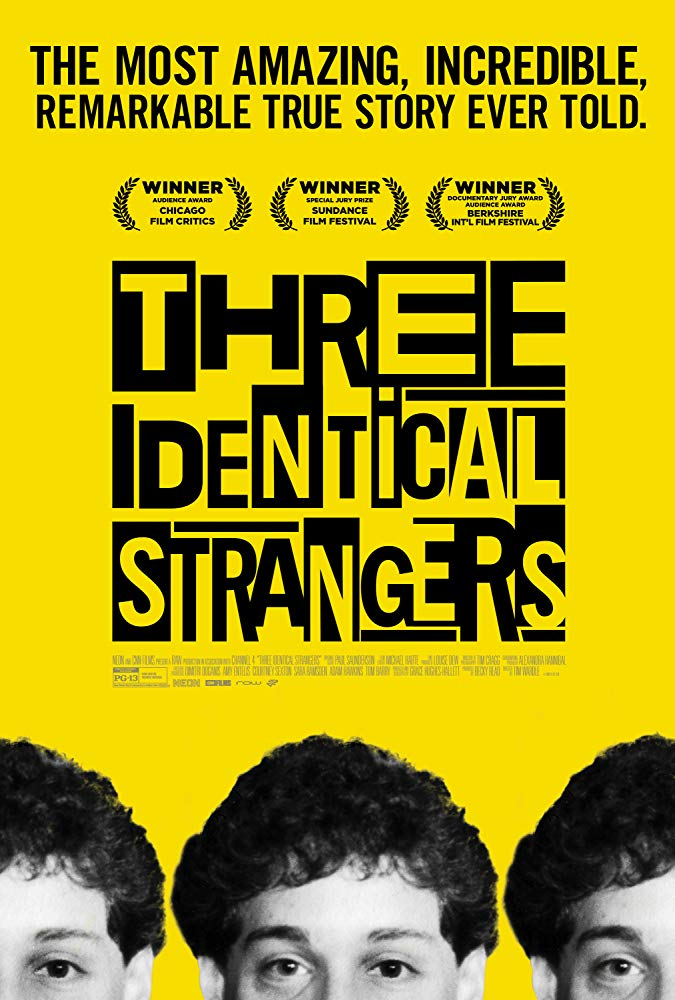 The film poster showing the top halfs of the heads of three guys in front of a yellow background.