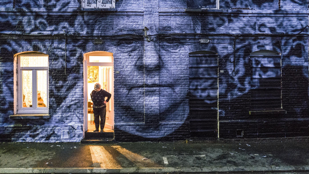 A woman standing in her doorway with a huge print of her own face across the house wall.