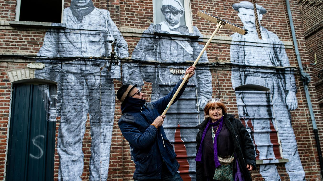 JR and Agnès Varda in front of three prints of workers on a house wall.