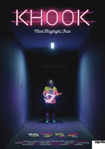 The film poster showing Hasan Majuni in a colorful outfit standing in a dark corridor.