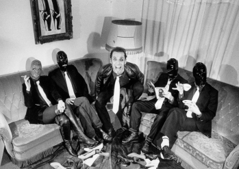 Black and white photo of Rosto with four people in BDSM masks grouped around him on two sofas.