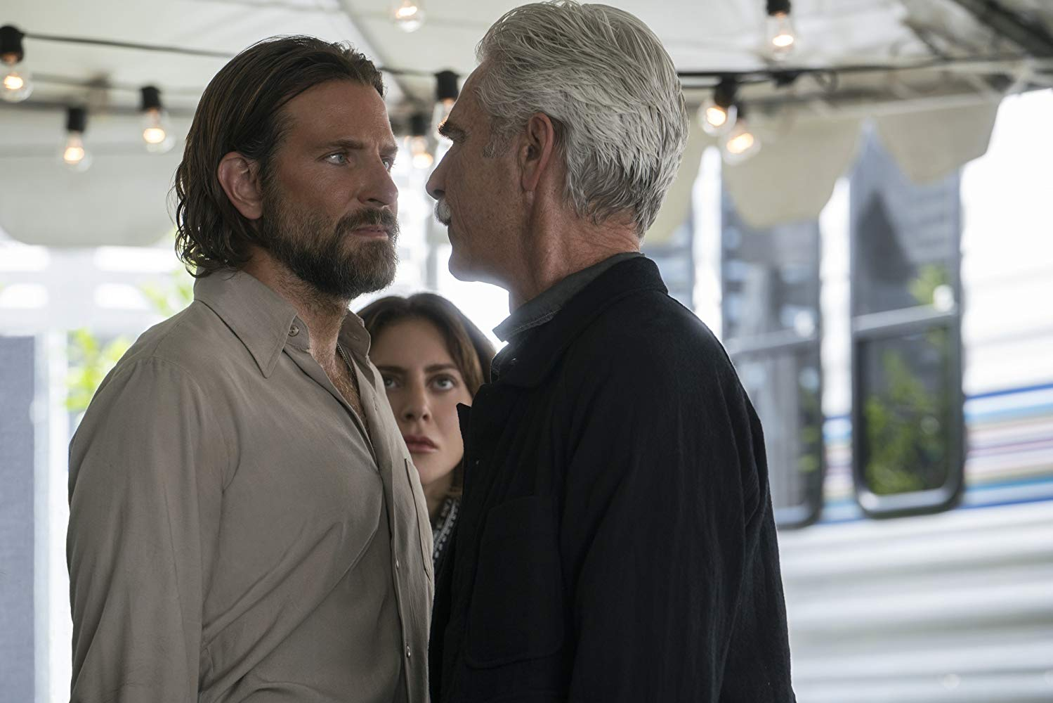 Jack (Bradley Cooper) facing his brother Bobby (Sam Elliott), with Ally (Lady Gaga watching in the background.