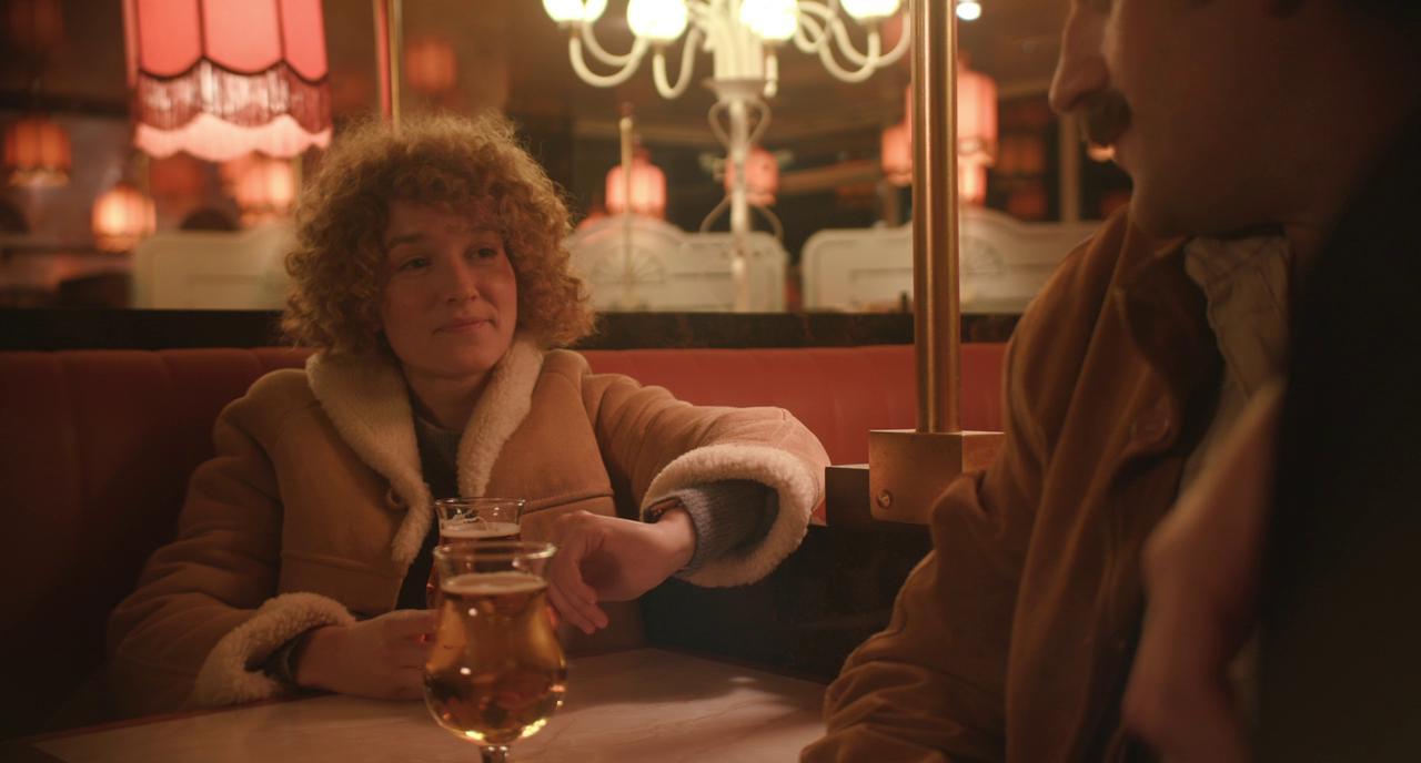 A woman (Anaïs Demoustier) sitting in a bar with a man (Grégoire Ludig).