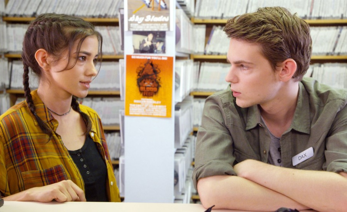 A teenage girl (Seychelle Gabriel) and boy (Robbie Kay) looking at each other.