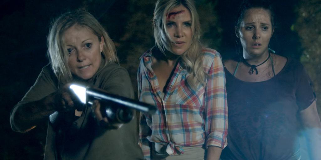 Three disheveled women, one of them pointing a shot gun at something.