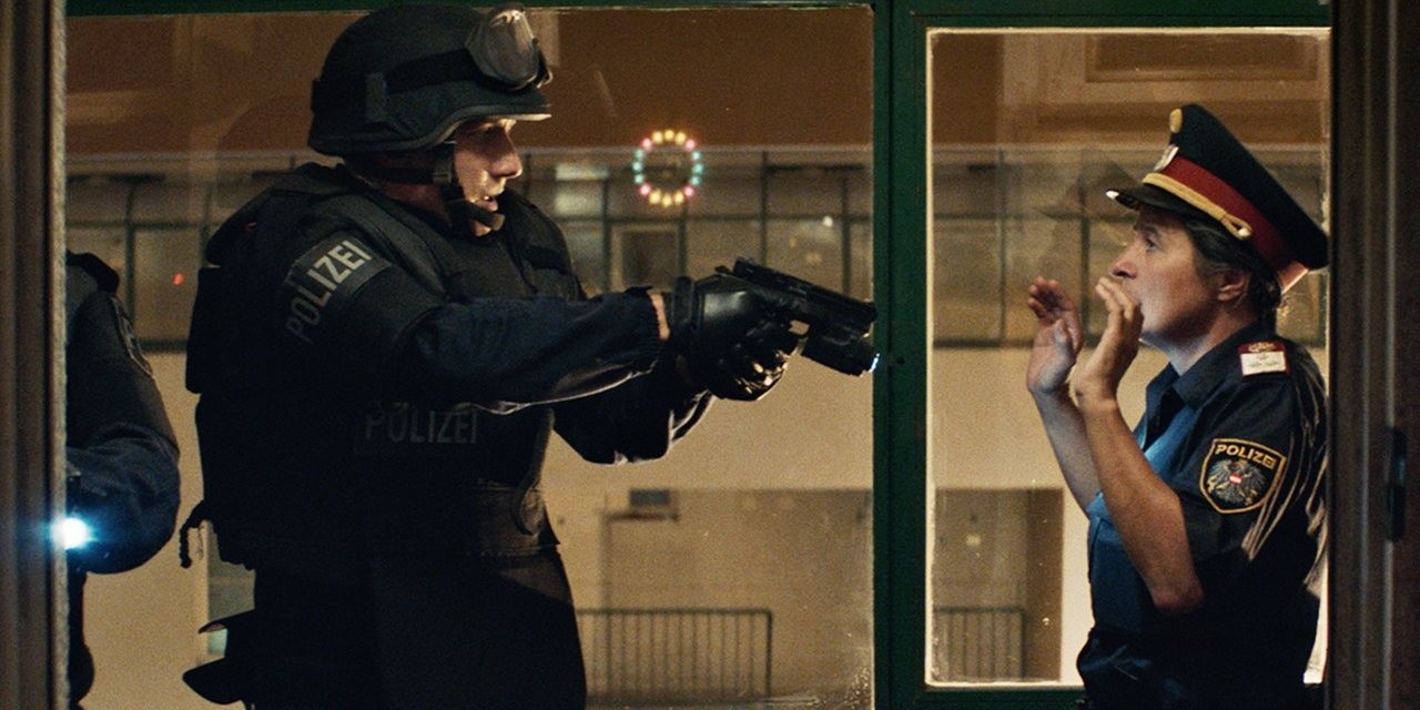 A special forces police officer (Laurence Rupp) in riot gear pointing a gun at a police officer in uniform (Maria Hofstätter).