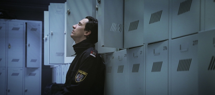 A police officer (Laurence Rupp) leaning against a wall of lockers.