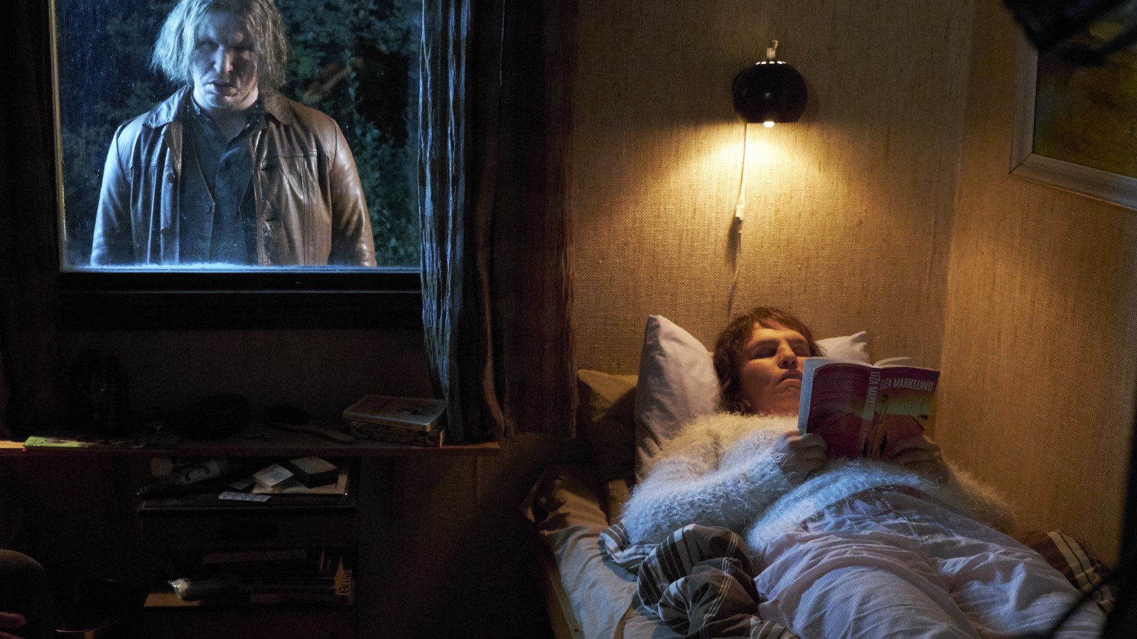 A woman (Eva Melander) lying on a bed reading, while a man (Eero Milonoff) is staring through her window into the room.