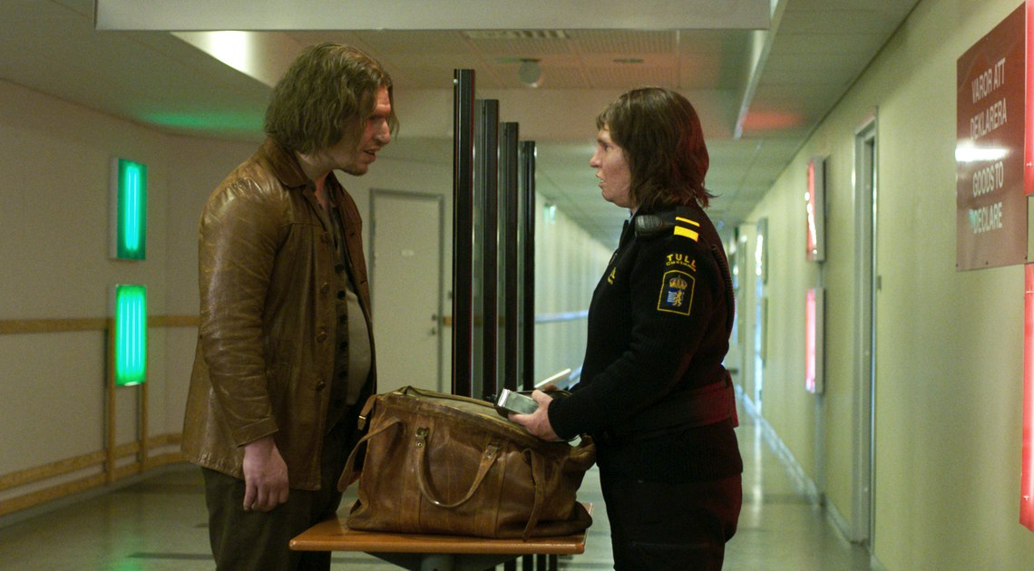 A man (Eero Milonoff) having his back searched by a custom agent (Eva Melander) at the airport.