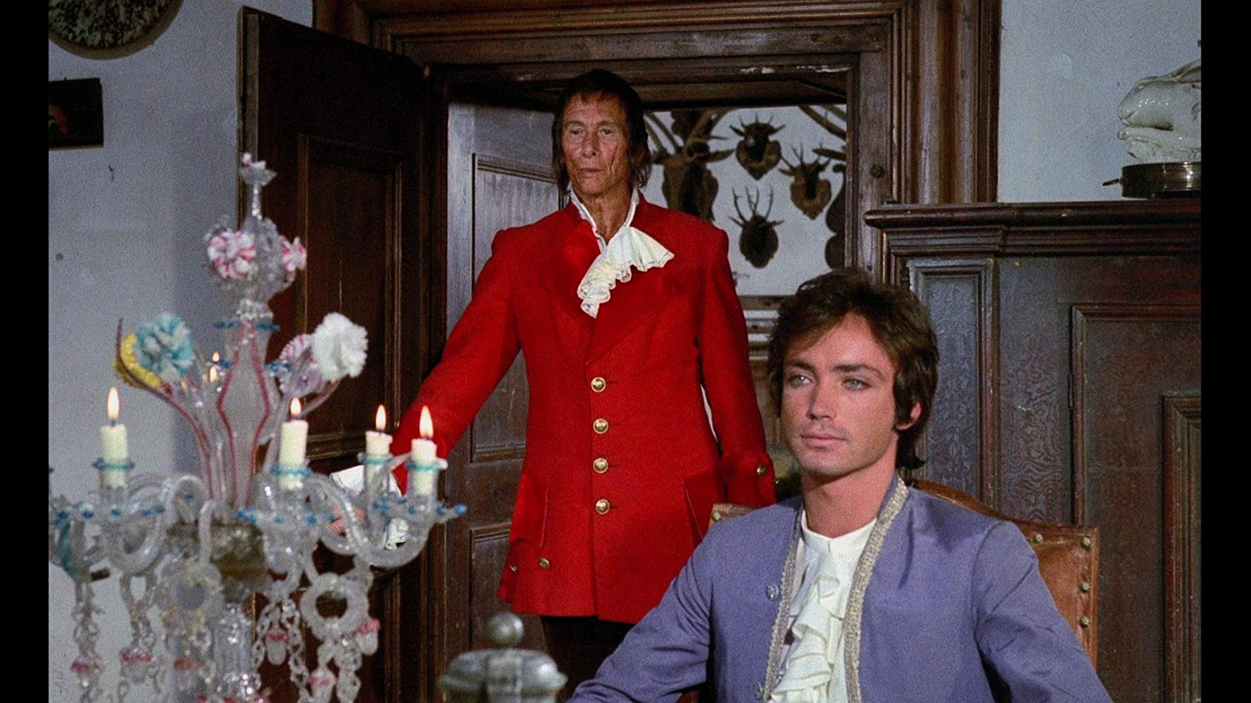A young man (Udo Kier) sits at the table as an older man (Reggie Nalder) enters the room behind him.