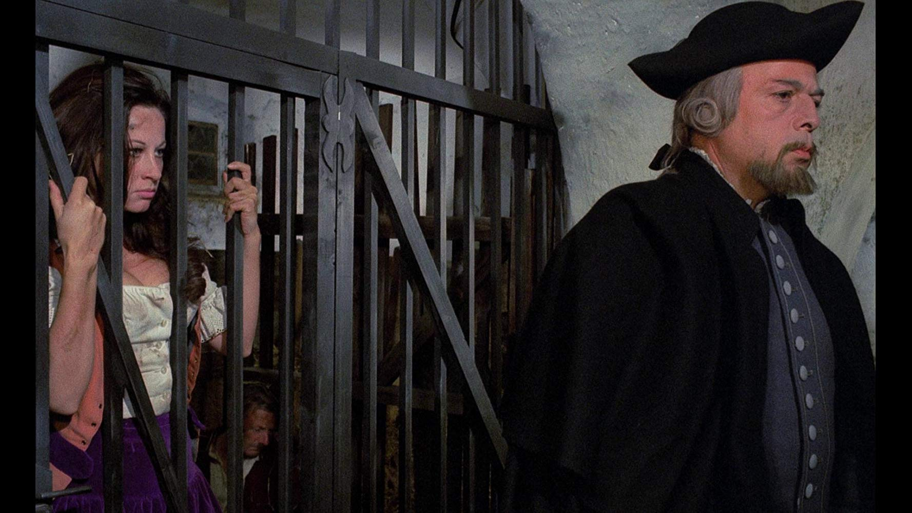 A young woman (Olivera Katarina) behind bars looking at an older man (Herbert Lom) with his back turned to her.