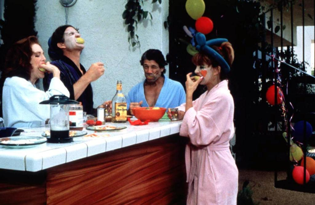 Two couples partly in clown make-up doing shots.