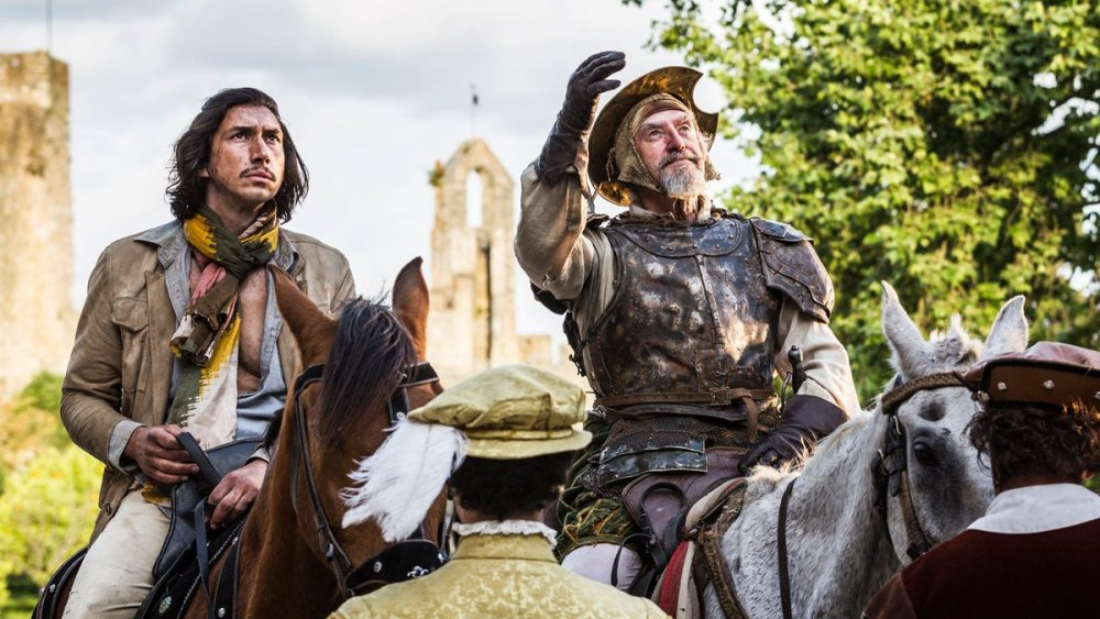 A younger man (Adam Driver) with a scarf and an older man (Jonathan Pryce) wearing a suit of armor on two horses.