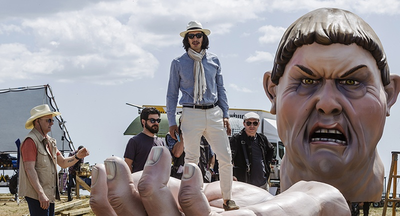 A young man (Adam Driver) with a fancy scarf and hat standing on a movie prop of a giant's hand, the giant's head visible in the background.