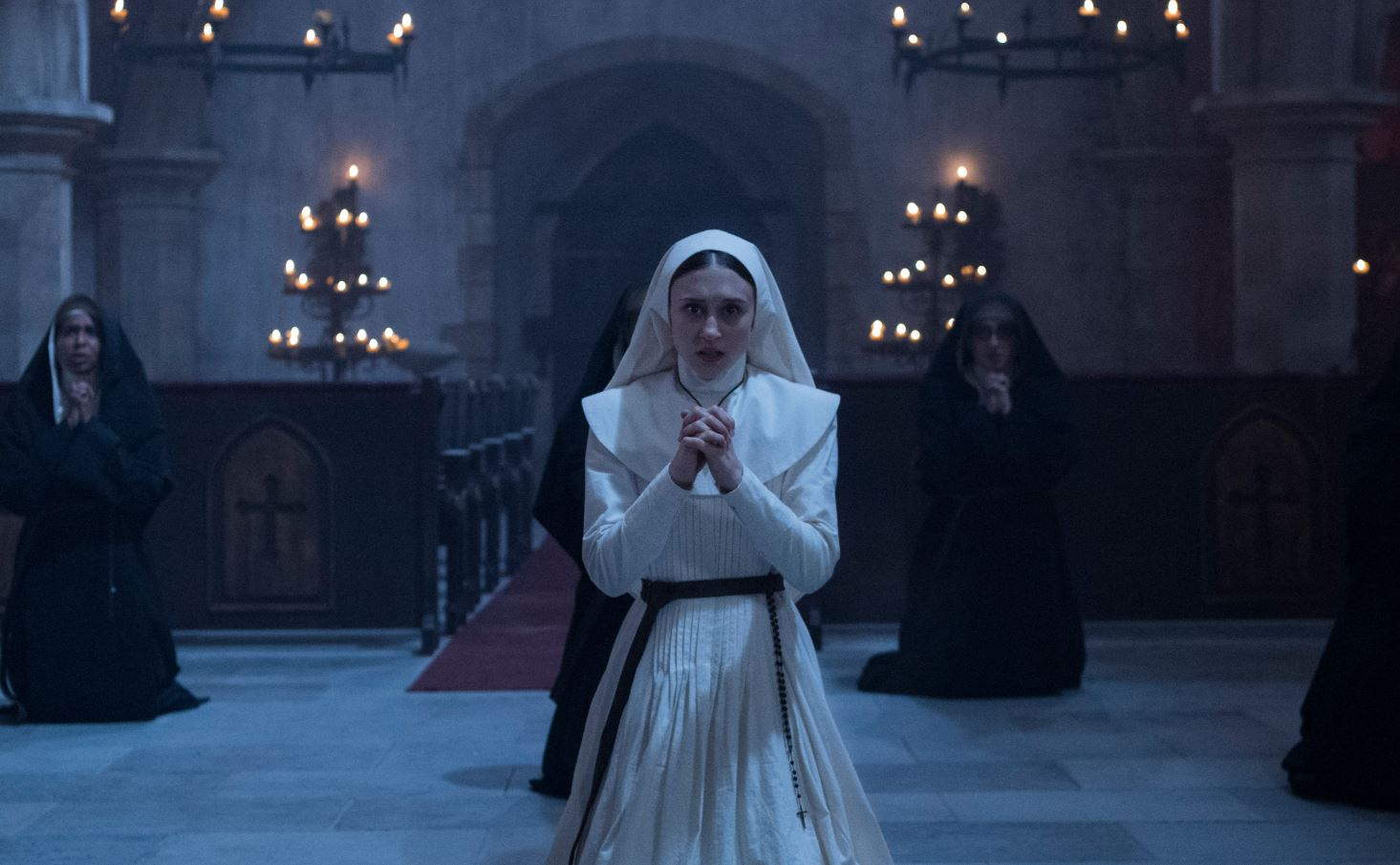 A young nun (Taissa Farmiga) kneeling in a church, praying.
