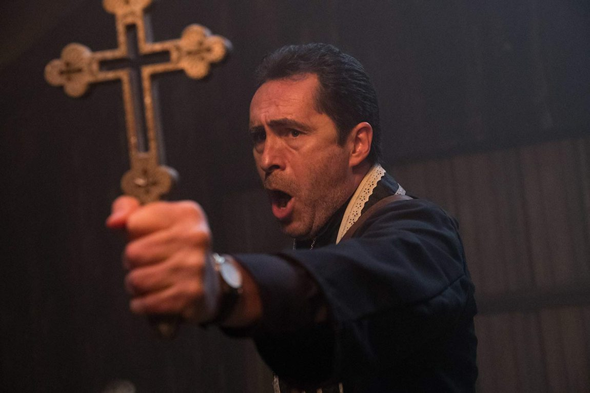 A priest (Demián Bichir) holding out a big cross against something while speaking.