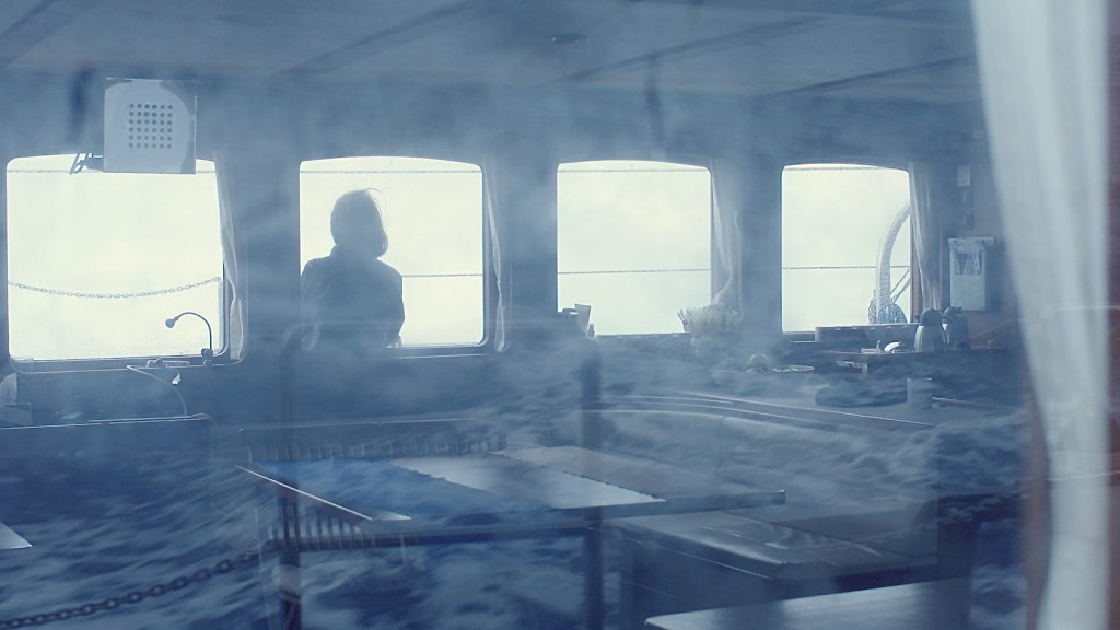 A douple exposure film still, showing a woman on a ship in one layer, and the sea in the other.