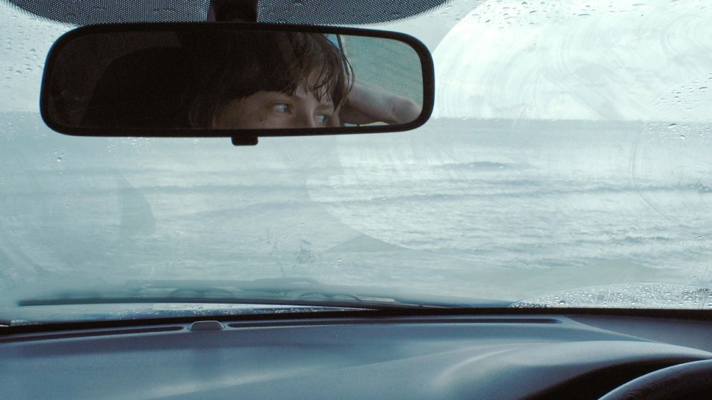 A view of the ocean from a car, a woman's eyes visible in the mirror.