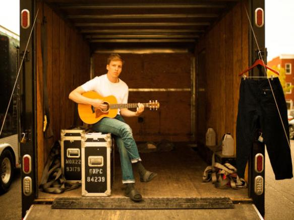 George Ezra sitting in an almost empty truck with a guitar in his lap.