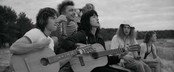 Viktor Tsoy (Teo Yoo) singing with a couple of guys at the beach.