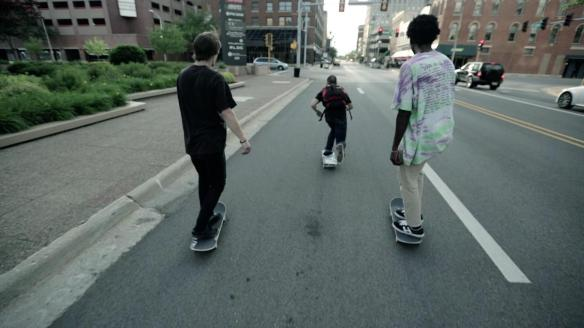 Three skateboarders rolling down the street.