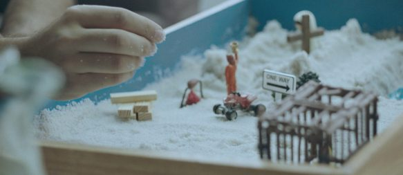 A sandbox with a child's hand that arranges tiny figures.