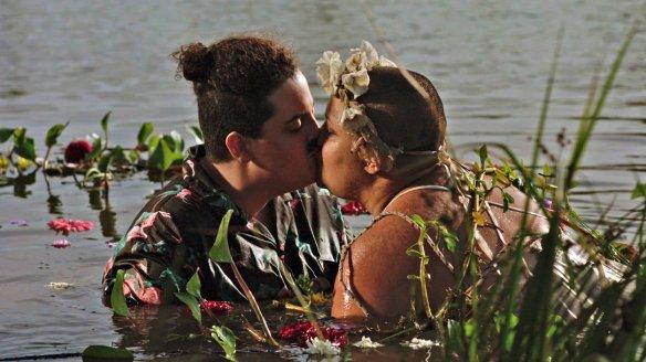 Two fat women kissing in a lake