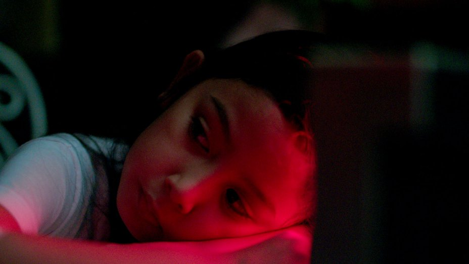 A girl with her head on her arms, bathed in red light.