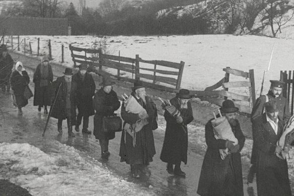 A line of people carrying bundles walks through the snow.