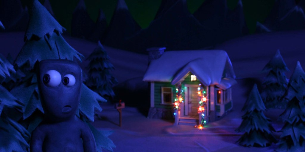 A clay figure in front of a house with holiday lights.