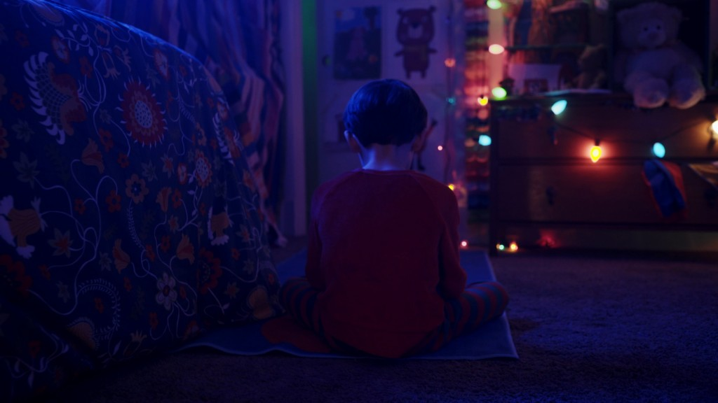 A boy sitting on his bed in a dark room, lit only by Christmas lights.