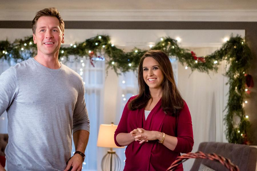 Peter (Paul Greene) and Sara (Lacy Chabert) in a festively decorated room.