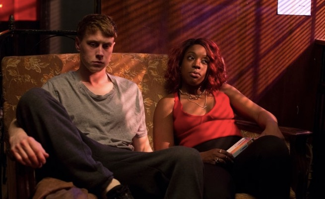 Gil (George MacKay) and Yvonne (Ronke Adekoluejo) sitting on a couch.