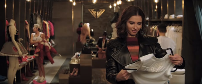 Elena (Naomi Scott) looking at clothes in a huge closet.