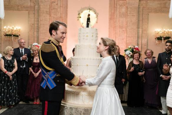 Amber (Rose McIver) and Richard (Ben Lamb) standing in front of a big wedding cake.