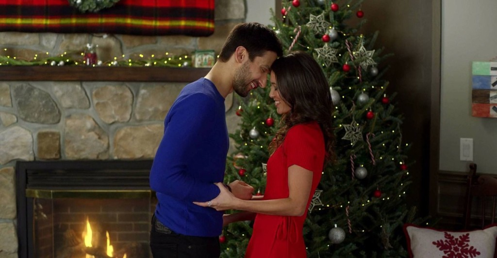 A woman (Kaitlyn Leeb) and a man (Scott Cavelheiro) leaning in for a kiss in front of a Christmas tree.