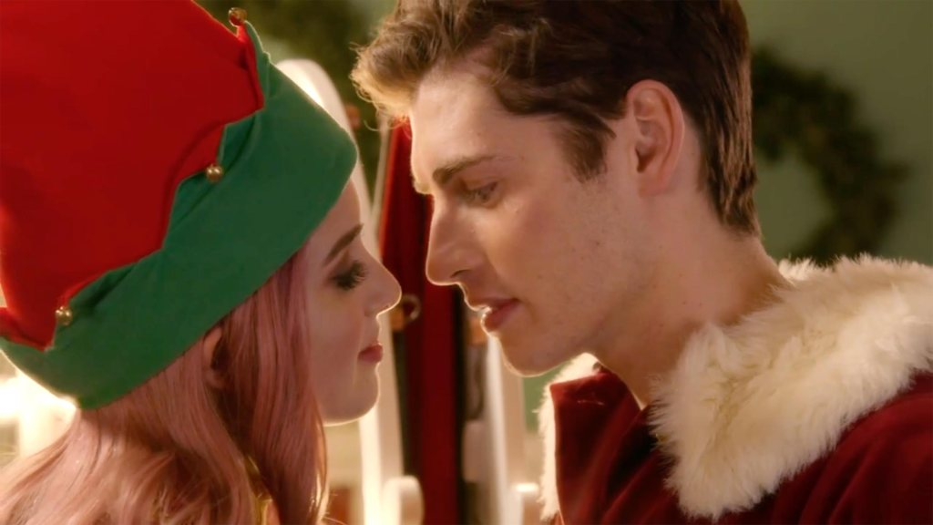 A young woman (Laura Marano) dressed as an elf and a young man (Gregg Sulkin) dresses as Santa Claus leaning in for a kiss.