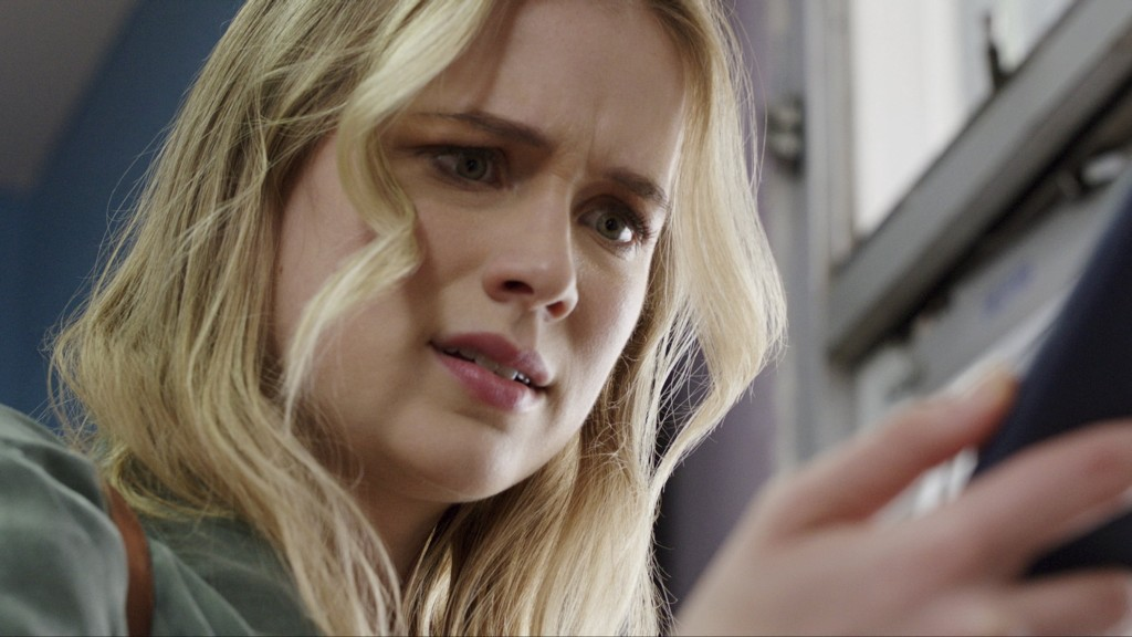 Quinn (Elizabeth Lail) staring at her phone.