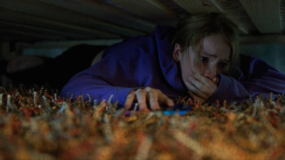 Jordan (Talitha Eliana Bateman) hiding under the bed.