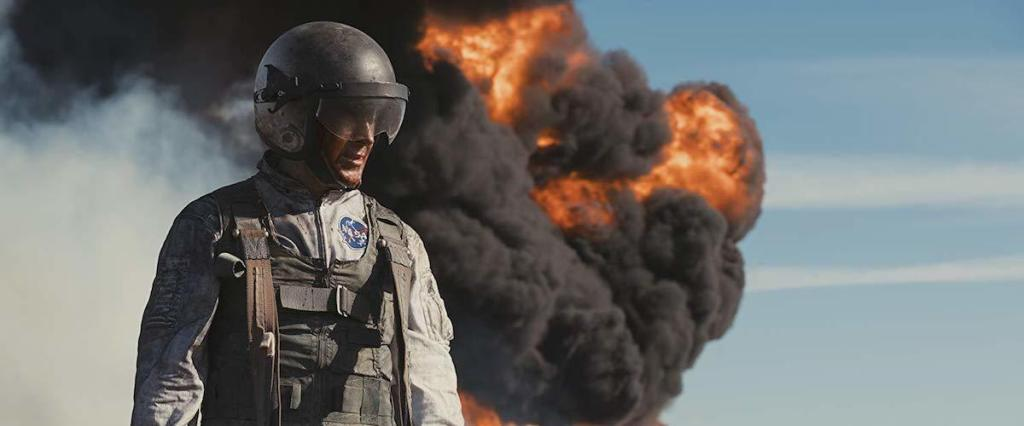 An astronaut (Ryan Gosling) in front of a column of smoke and flame.