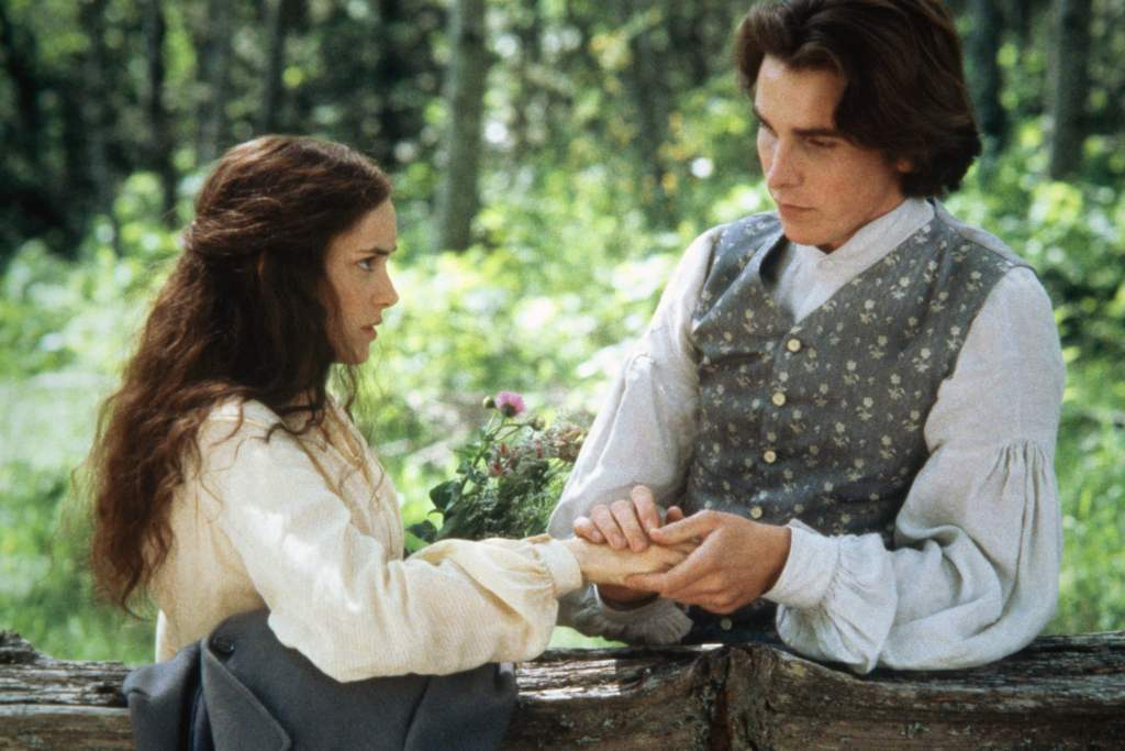 Jo March (Winona Ryder) looks shocked as Laurie (Christian Bale) holds her hand.