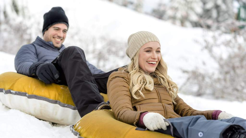 A man (Thomas Beaudoin) and a woman (Katrina Bowden) sledding in inflatable donuts.