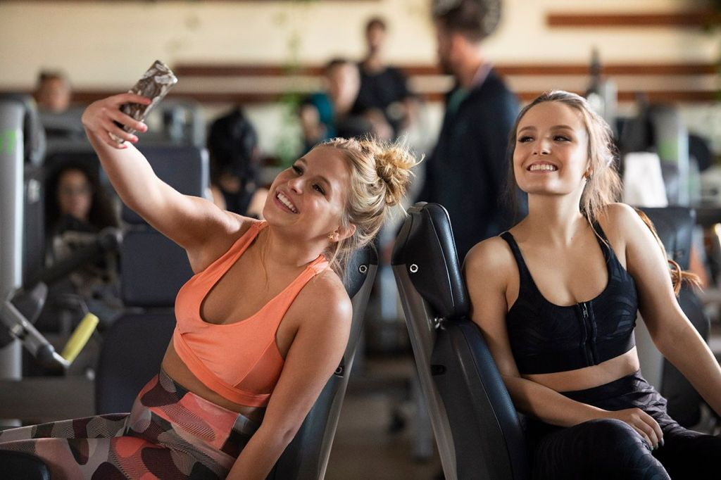 Ana (Larissa Manoela) and her best friend Mara (Amanda Orestes) taking a selfie in the gym.