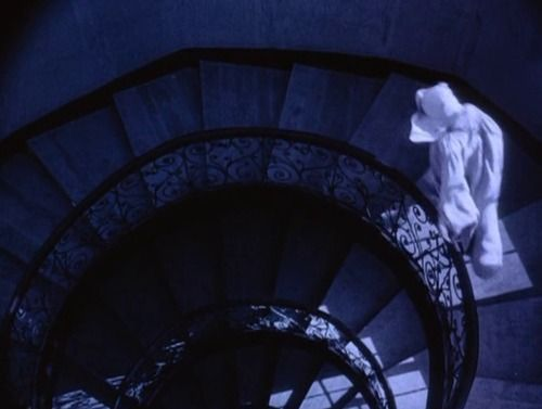 A nun walking down a flight of stairs.