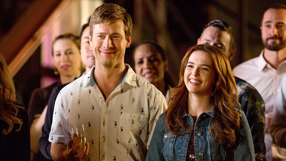 Charlie (Glen Powell) and Harper (Zoey Deutch) standing next to each other, smiling.