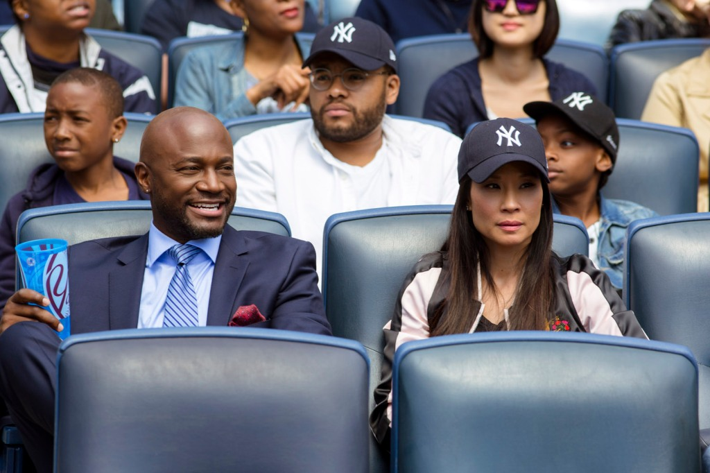 Rick (Taye Diggs) and Kirsten (Lucy Liu) at a sports game.