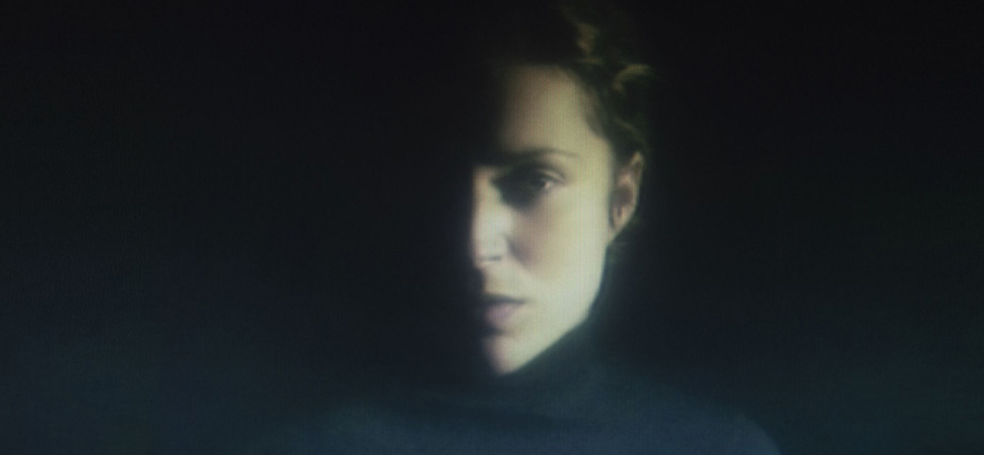 A portrait shot of Agnes Obel in front of a black background. It is slightly out of focus.